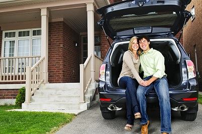 Couple sitting on their car in front of their home